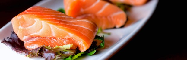 Three pieces of Salmon over mixed greens